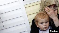 «Կոնտեյներային քաղաք» անվանումը ստացած՝ Թուրքիայի հարավում գտնվող ճամբարի բնակիչ մի կին իր երեխայի հետ, 22 հուլիսի 2012թ.
