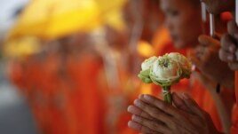 A Buddhist monk holds flowers as he joins others waiting for the coffin of the former king Norodom Sihanouk to arrive at the Royal Palace in Phnom Penh October 17, 2012. Tens of thousands poured into Cambodia's capital to witness the procession on Wednesday.