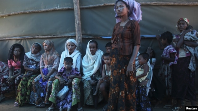 Shofica Belcom, 25, waits with other mothers at a Burma Red Cross health clinic near Sittwe, capital of Burma's Rakhine state, October 14, 2012.