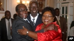 FILE: Zimbabwean President Robert Mugabe, left, celebrates with newly sworn-in vice presidents Joyce Mujuru, right, and the late Joseph Msika, center, State House, Harare, Oct. 2008 file photo.