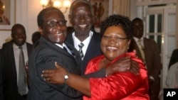 FILE: IN GOOD TIMES - Zimbabwean President Robert Mugabe, left, celebrates with newly sworn-in vice presidents Joyce Mujuru, right, and Joseph Msika, center, State House, Harare, Oct. 2008 file photo.