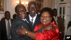 Zimbabwean President Robert Mugabe, left, celebrates with newly sworn-in vice presidents Joyce Mujuru, right, and Joseph Msika, center, State House, Harare, Oct. 2008 file photo.