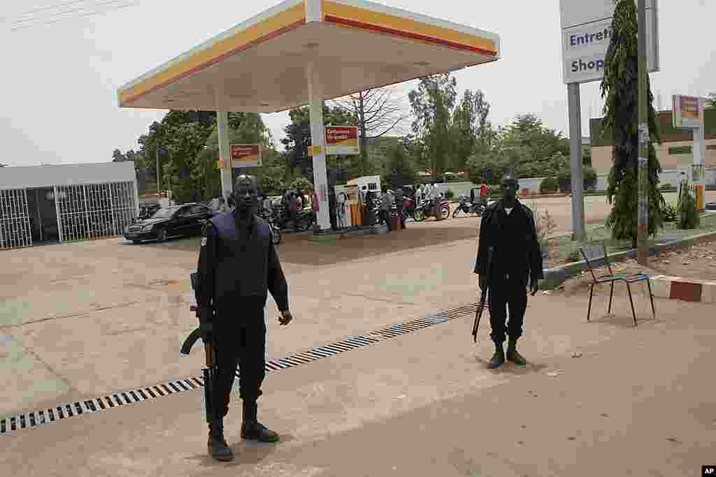 Police stand guard as drivers wait at a gas station, during fuel shortages following a military coup, in Bamako, Mali, March 24, 2012. (AP)