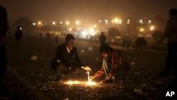 Warga India menyalakan lilin dekat Istana Kepresidenan di New Delhi, India, Sabtu (22/12). Polisi menggunakan gas air mata dan meriam air untuk membubarkan massa yang berusaha masuk ke istana saat menyuarakan tuntutan keadilan bagi korban pemerkosaan di bus oleh sekelompok anggota gang di kota tersebut.