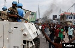 FILE - Residents chant slogans against Congolese President Joseph Kabila as UN peacekeepers patrol during demonstrations in the streets of the Democratic Republic of Congo's capital Kinshasa, Dec. 20, 2016.