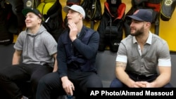 FILE - Boston Bruins players, from left, Frank Vatrano, Noel Acciari and Tyler Randell sit in the locker room during an end of season media availability at TD Garden in Boston.
