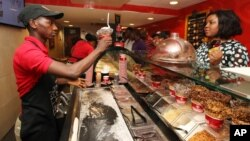 FILE - Customers buy Cold Stone ice cream in Lagos, Nigeria, Feb. 10, 2013. Years of solid economic growth, gradual economic reforms and energy discoveries have transformed Africa from a basket case into one of the world's hottest markets.