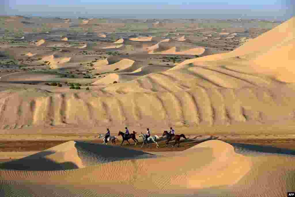 在阿联酋首都阿布扎比附近的一个村庄,参加谢赫.扎耶德.本.苏丹.阿勒纳哈扬国际赛马节的人们骑着马在沙丘中行进。