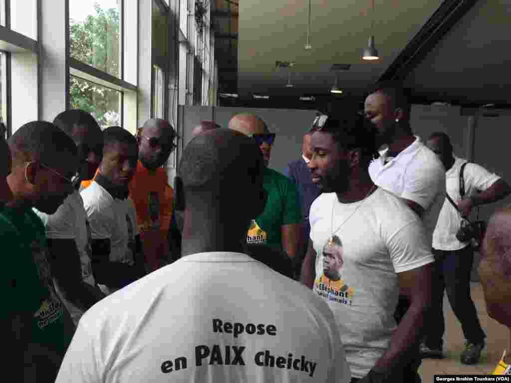 """Des Ivoiriens avec un tee-shirt """"repose en paix Cheiky"""", à l'aéroport d'Abidjan, le 15 juin 2017. (VOA/Georges Ibrahim Tounkara)"""