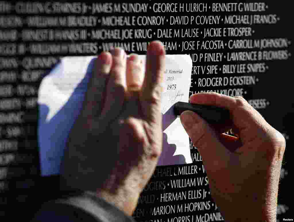 Chris Banholzer copies the name of a classmate from the Vietnam Moving Wall during Veterans Day weekend, Aurora, Illinois, Nov. 10, 2013.