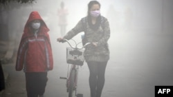 FILE - A woman walks with her child on a street as schools were closed due to the heavy smog in Jilin, northeast China's Jilin province.