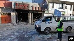 Công nhân Palestine quét dọn các mảnh vỡ trên đường phố ở thành phố Gaza, ngày 17/7/2014.