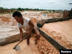 Seorang penambang sedang memisahkan pasr timah di sebuah tambang timah di Bangka (REUTERS/Beawiharta)