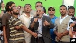 穆斯林兄弟会精神领袖穆罕默德•巴迪在开罗登台对数万支持者发表讲话,军队的直升机在上空盘旋。(2013年7月5日)