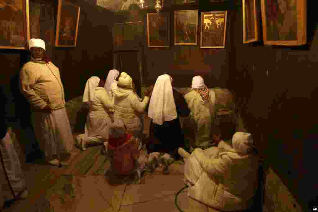 Christian pilgrim worshippers from Nigeria pray in the Grotto of the Church of Nativity in the West Bank town of Bethlehem on Christmas Eve, Dec. 24, 2013.