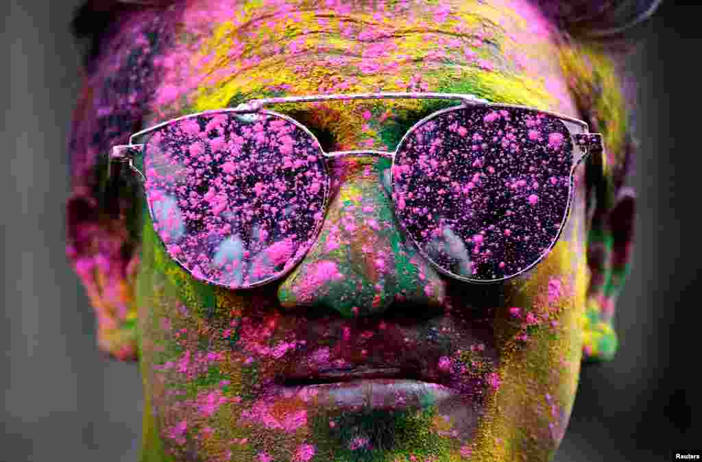 A man smeared in coloured powder poses during Holi celebrations in Kolkata, India.