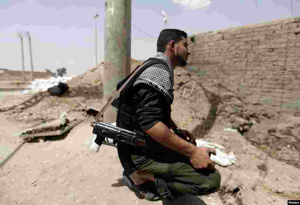 A Free Syrian Army fighter holds his weapon in Raqqa province, east Syria, May 6, 2013.
