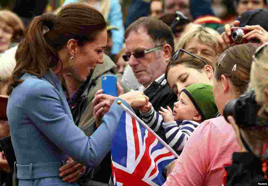 Catherine (L), Duchess of Cambridge, holds the hand of a baby in the crowd after laying a wreath with her husband, Britain's Prince William, at the war memorial in Seymour Square in the town of Blenheim, New Zealand.