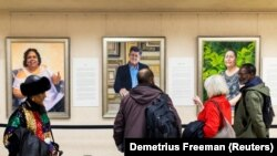 """Visitors examine Betsy Ashton's exhibition, """"Portraits of Immigrants"""" at Riverside Church in New York, U.S."""