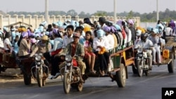 Cambodian garment factory workers travel together in motor carts to get home from work at the Sala Lek Pram village, Kampong Chhnang province.