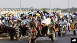 File Photo: Cambodian garment factory workers travel together in motor carts to get home from work at the Sala Lek Pram village, Kampong Chhnang province.