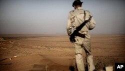 图为一名利比亚反叛人员7月15日监控卡扎菲军队的动向