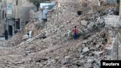 A civilian collects tree branches amid the rubble of a damaged site in the rebel-held besieged Qadi Askar neighborhood of Aleppo, Syria, Nov. 24, 2016.