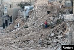 ພົນລະເຮືອນຄົນນຶ່ງກຳລັງເກັບເອົາງ່າໄມ້ ທ່າມກາງຄວາມພິນາດ ໃນເມືອງ Aleppo.