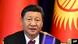 FILE - Chinese President Xi Jinping attends a joint news conference with Kyrgyzstan's President Sooronbai Jeenbekov, in Bishkek, Kyrgyzstan, June 13, 2019.