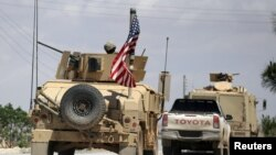 FILE - The U.S. flag flutters on a military vehicle in Manbij countryside, Syria, May 12, 2018.