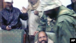 A mobile phone picture taken by one of his guards shows Saif al-Islam Gaddafi sitting with his captors in Obari airport November 19, 2011