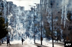 Palestinian stone throwers run to take cover after Israeli security forces fired tear gas canisters during clashes following a demonstration next to the Israeli controversial separation wall in the West Bank city of Bethlehem, Dec. 18, 2015.