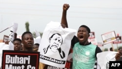 A protester shouts and raises his fist during a demonstration in Abuja on June 12, 2021, as Nigerian activists called for nationwide protests over what they criticize as bad governance and insecurity in Nigeria.