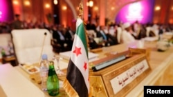 پرچم شورای ائتلاف ملی سوریه در نشست اتحادیه عرب در قطر، سه شنبه ۲۶ مارس ۲۰۱۳