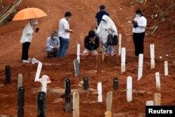 Kerabat berkabung saat pemakaman anggota keluarganya di area pemakaman yang disediakan pemerintah untuk korban Covid-19 di kompleks pemakaman Pondok Ranggon, Jakarta, 24 September 2020. (Foto: Reuters)