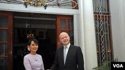 Ikon demokrasi Burma Aung San Suu Kyi (kiri) berjabat tangan dengan Menlu Inggris William Hague di depan kediaman duta besar Inggris di Yangon (5/1)