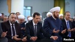 Presiden Suriah Bashar al-Assad (kedua dari kiri) menghadiri sholat Idul Adha di masjid al-Nu'man bin Bashir di Damaskus 4 Oktober 2014.