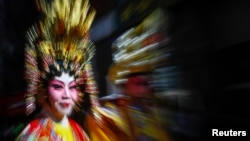 A woman dressed in traditional wear takes part in the 14th annual Chinatown Lunar New Year Parade in New York, February 17, 2013.