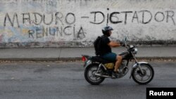"""FILE - A man on a motorcycle rides past a mural that reads, """"Maduro. Dictator. Resign"""" during a blackout in Caracas, Venezuela, March 27, 2019."""
