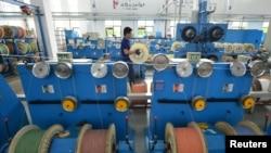 中國的工廠活動10月份增長速度稍慢,但略高於分析師的預期。圖為中國浙江省湖州市的一個通訊設備廠光纖生產線上的工人在工作。 (路透社2019年5月15日資料照)