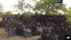 FILE - In this photo taken from video released by Nigeria's Boko Haram terrorist network, May 12, 2014, shows missing girls abducted from the northeastern town of Chibok.