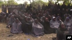 In this file photo taken from video released by Nigeria's Boko Haram terrorist network, May 12, 2014, shows missing girls abducted from the northeastern town of Chibok. A teenage who surrendered before carrying out a suicide bombing attack in northern Cameroon has told authorities she was one of the 276 girls abducted from a Nigerian boarding school by Islamic extremists nearly two years ago, authorities said Saturday, March 26, 2016. (AP Photo)