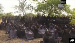 FILE - This file photo taken from video released by Nigeria's Boko Haram terrorist network, May 12, 2014, shows missing girls abducted from the northeastern town of Chibok.