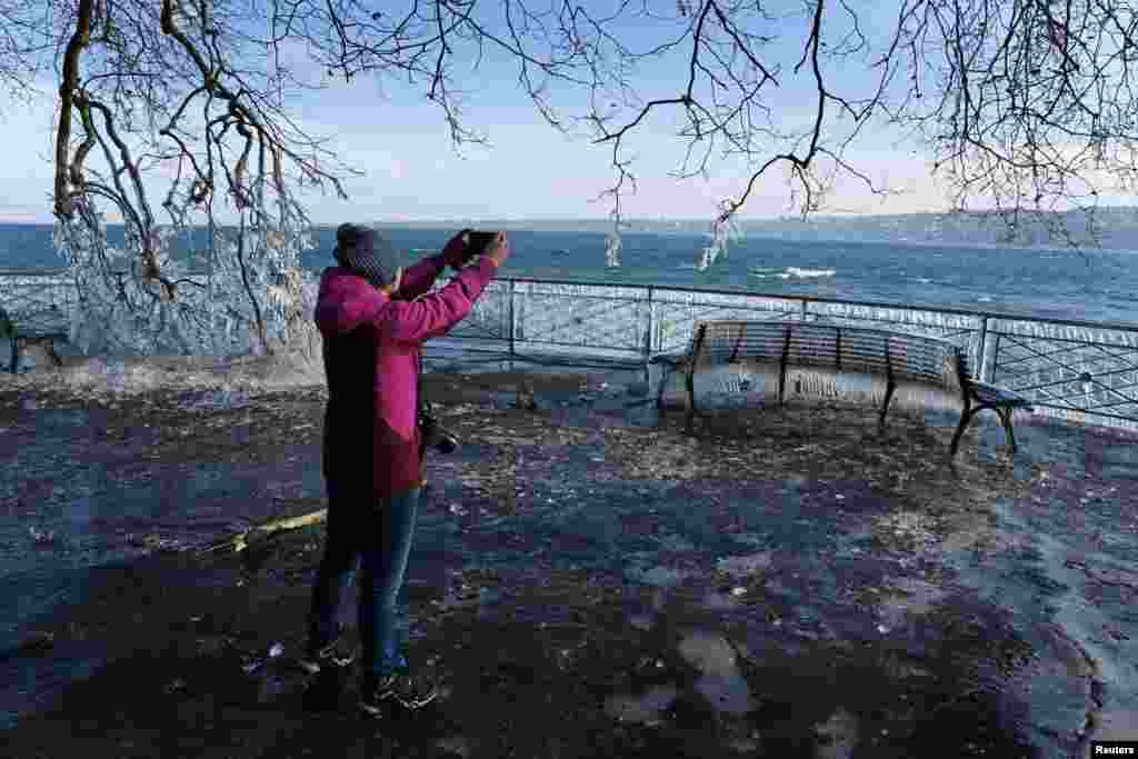 A woman takes pictures of the frozen lakeside due to the strong wind conditions in Geneva, Switzerland.