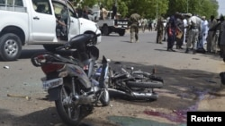 FILE - Security officers are seen standing at the site of a suicide bombing in Ndjamena, Chad, June 15, 2015. Ten men were executed Saturday in connection with this and another attack.