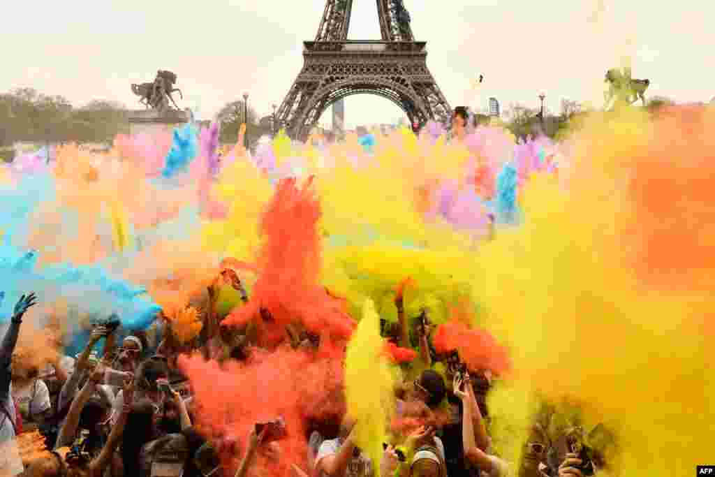 People throw colored powder as they celebrate finishing their five kilometers in the Color Run 2018 at the Eiffel Tower in Paris, France.