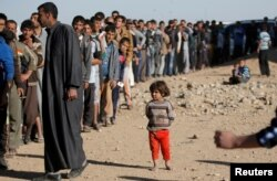 A child stands next to men who are waiting in line for food donated by an Iraqi government organization at the outskirts of Mosul, Iraq, Nov. 20, 2016.