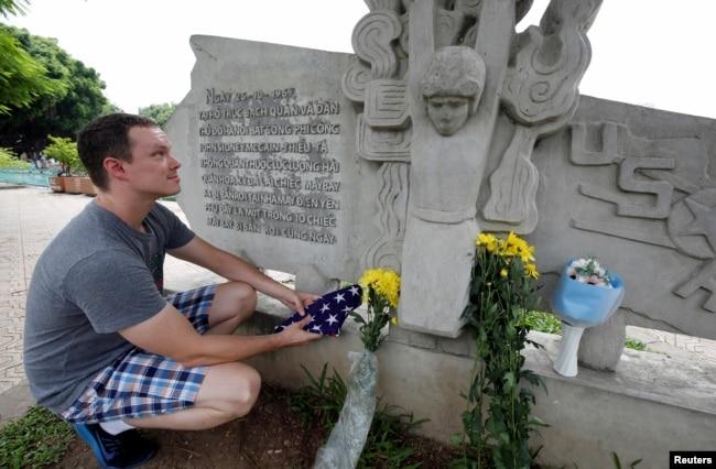 English teacher Derek Davis from the U.S. places a U.S. flag and flowers in memory of the late U.S. Senator John McCain (R-Az.) at the McCain Memorial in Hanoi, Vietnam, Aug. 26, 2018.
