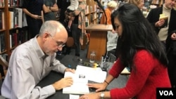 "Author John Burgess with VOA Khmer reporter Manilene Ek at the book signing of his latest work, ""The Stairway Guide's Daughter,"" at Politics and Prose bookstore, Washington DC, November 19, 2017. (Photo: VOA Khmer)"