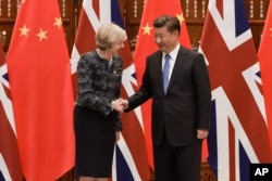 FILE - Chinese President Xi Jinping, right, shakes hand with British Prime Minister Theresa May, prior to their meeting, at the West Lake State House, in Hangzhou, China, Sept. 5, 2016.